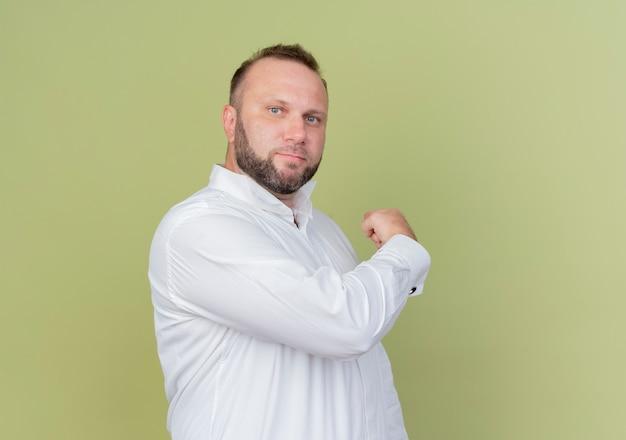Homme barbu portant une chemise blanche avec une expression confiante pointant vers l'arrière debout sur un mur léger
