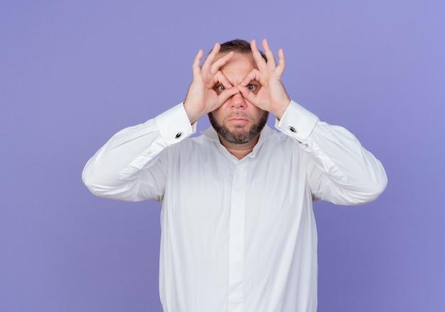 Homme barbu portant une chemise blanche à la recherche de geste binoculaire avec les doigts regardant à travers les doigts debout sur le mur bleu