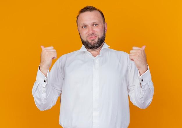 Homme barbu portant une chemise blanche souriant pointant vers l'arrière debout sur un mur orange