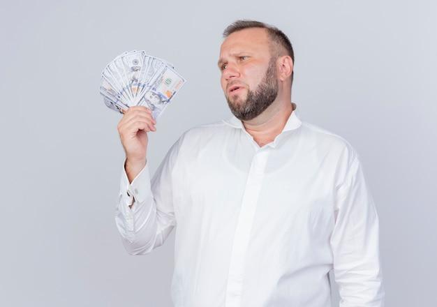 Homme barbu portant une chemise blanche tenant de l'argent à côté avec une expression triste debout sur un mur blanc