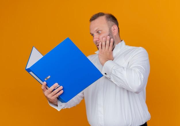 Homme barbu portant une chemise blanche tenant un dossier bleu en le regardant surpris et étonné sur orange