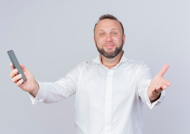 Homme barbu portant une chemise blanche tenant un smartphone faisant un geste de bienvenue avec la main souriant debout sur un mur blanc