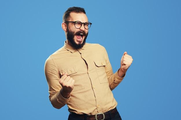 Un homme barbu portant des lunettes agit comme s'il avait gagné quelque chose avec un espace de copie