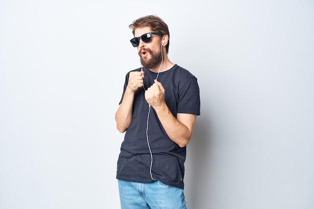 Homme barbu portant des lunettes écoutant de la musique sur un casque de style de vie en studio