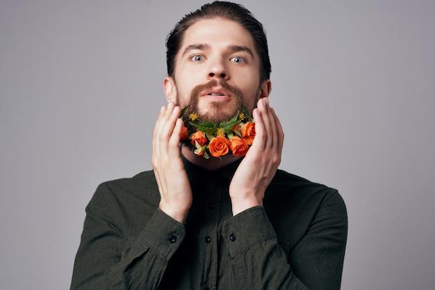 Homme barbu posant des fleurs dans un style de vie de studio de mode barbe