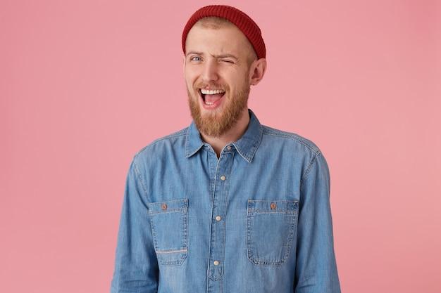 Homme barbu positif avec une chemise en jean à la mode, un chapeau rouge, une expression ludique, des clins d'œil, la bouche ouverte, encourage les supports, isolé expressions faciales humaines, langage corporel