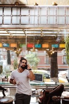 Homme barbu positif parlant au téléphone en se tenant debout dans le bar