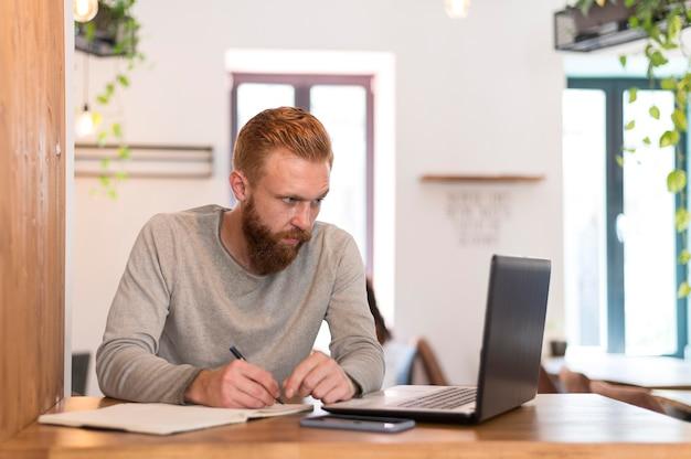 Homme barbu, prendre des notes au travail
