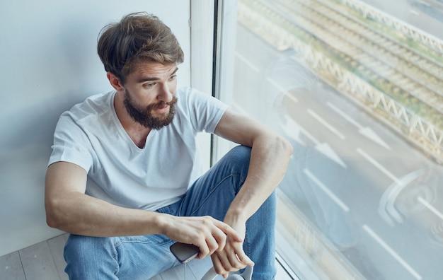 Homme barbu près de la fenêtre à la maison avec intérieur de la technologie internet de téléphone