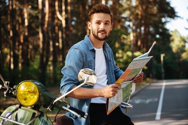 Homme barbu près de scooter en regardant la carte à l'extérieur.