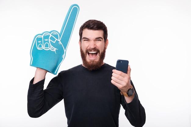 Un homme barbu qui crie tient son téléphone et son gant de doigt en mousse!