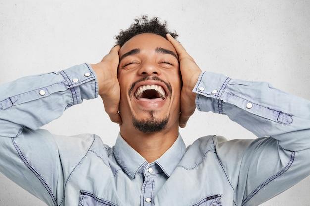 Un homme barbu de race mixte excité sourit joyeusement, garde les mains sur la tête, ferme les yeux, se sent étonné