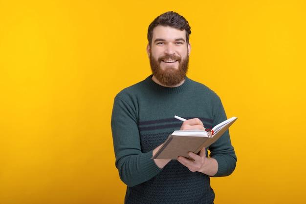 Un homme barbu regardant la caméra écrit quelque chose dans son journal.