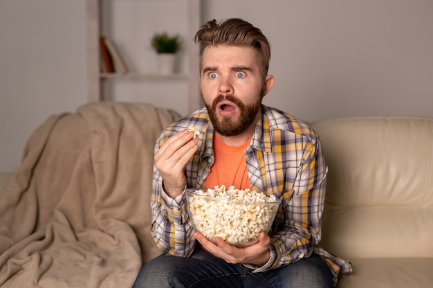 Homme barbu regardant un film ou des jeux de sport tv manger du pop-corn dans la maison la nuit. cinéma, championnat