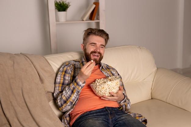 Homme barbu regardant un film ou des jeux de sport tv manger du pop-corn dans la maison la nuit.