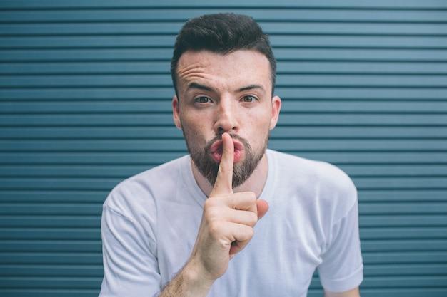 Un homme barbu regarde la caméra et montre le symbole du silence. il garde le doigt sur la bouche. isolé sur rayé