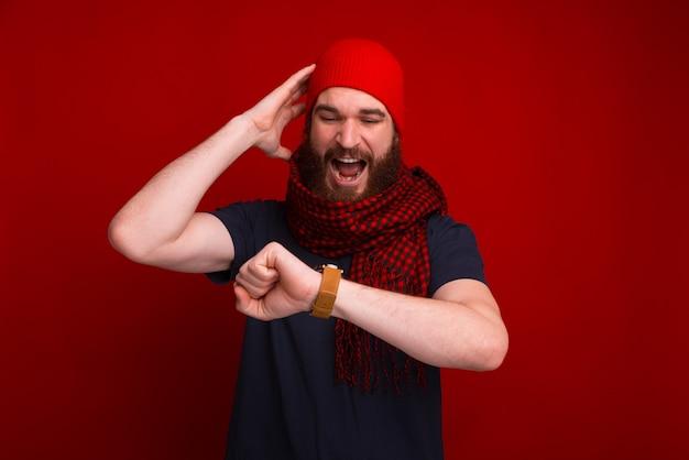 Un homme barbu regarde stupéfait sa montre près d'un mur rouge.
