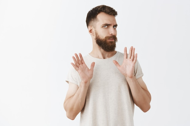 Homme barbu réticent et dérangé posant contre le mur blanc