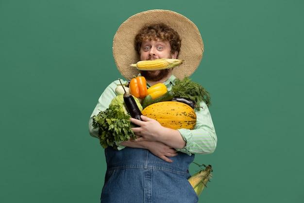 Homme barbu roux, agriculteur avec récolte de légumes isolé sur le mur vert du studio.