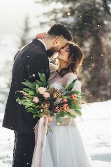 Homme barbu et sa belle épouse posent sur la neige dans une forêt d'hiver magique