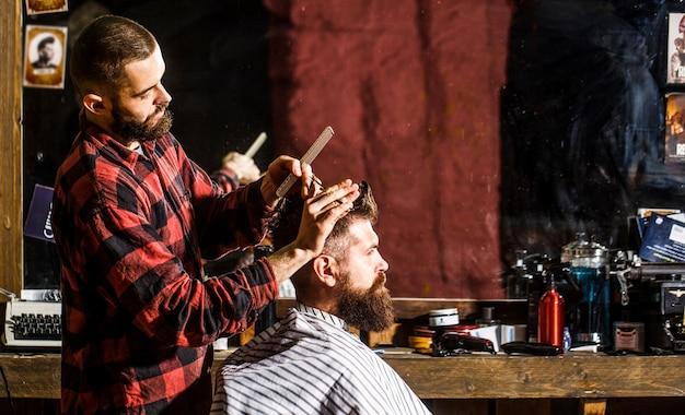 Homme barbu en salon de coiffure. travailler dans le salon de coiffure. coiffeur coupant les cheveux d'un client masculin. coiffeur au service du client au salon de coiffure. homme visitant un coiffeur dans un salon de coiffure.