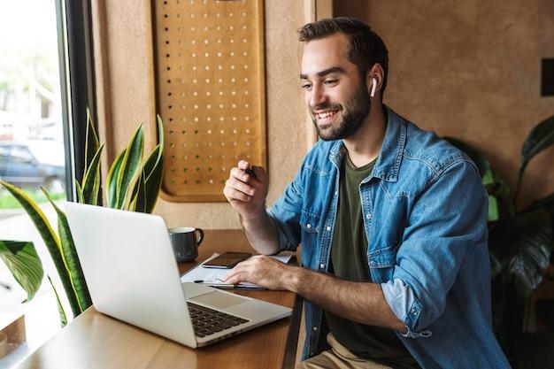 Homme barbu satisfait portant une chemise en jean écrivant des notes et tapant sur un ordinateur portable tout en travaillant dans un café à l'intérieur