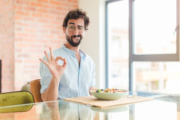 Homme barbu se sentant heureux, détendu et satisfait, montrant son approbation avec un geste correct, souriant
