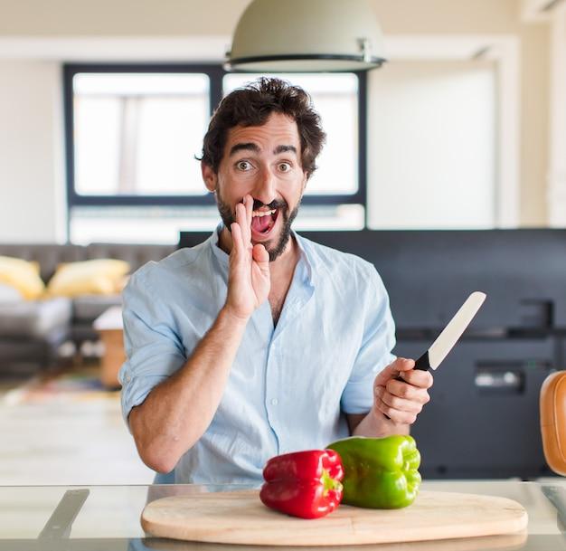 Homme barbu se sentant heureux, excité et positif, donnant un grand cri avec les mains à côté de la bouche, appelant