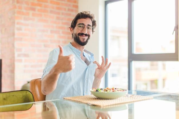 Homme barbu se sentir fier, insouciant, confiant et heureux, souriant positivement avec les pouces vers le haut