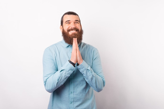 Un homme barbu se tenant la main prie, espérons-le, pour un miracle.