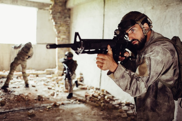 Un homme barbu se tient devant avec un fusil.