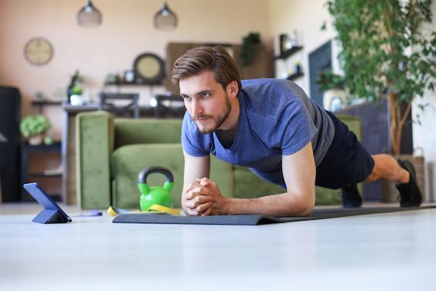Homme barbu séduisant faisant des exercices de planche à la maison pendant la quarantaine. la forme physique est la clé de la santé.