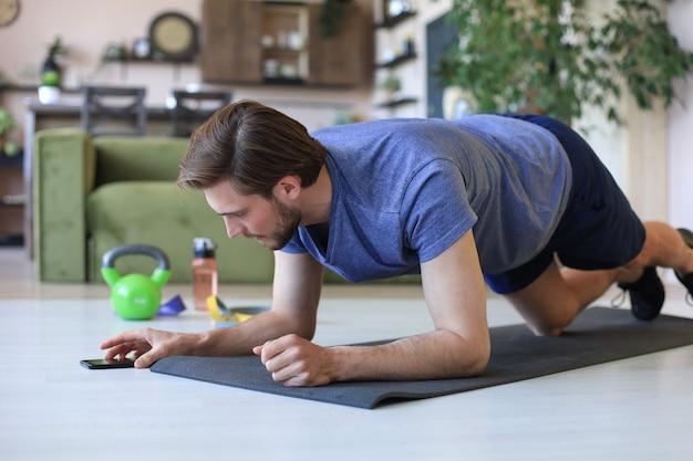 Homme barbu séduisant regardant dans un smartphone et faisant des exercices de planche à la maison pendant la quarantaine. la forme physique est la clé de la santé.