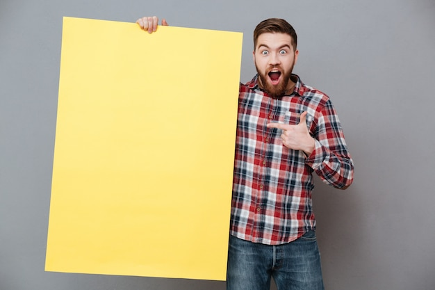 Homme barbu séduisant tenant un tableau blanc et pointant