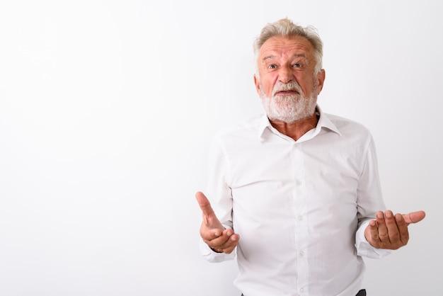 Homme barbu senior en colère avec les deux bras levés sur blanc