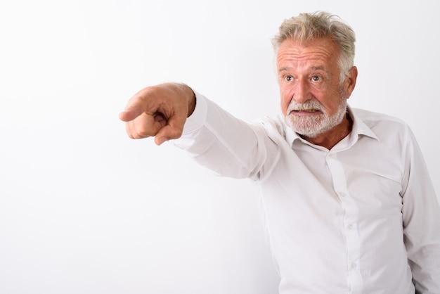 Homme barbu senior en colère, doigt pointé sur blanc