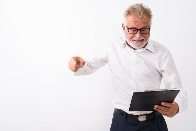 Homme barbu senior en colère lisant sur le presse-papiers tout en pointant le doigt avec des lunettes sur blanc