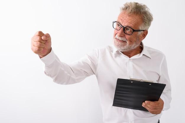 Homme barbu senior en colère pensant tout en frappant l'air et tenant le presse-papiers avec des lunettes sur blanc