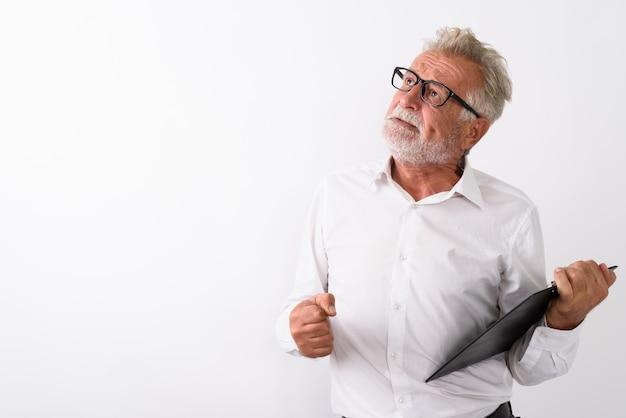 Homme barbu senior en colère pensant tout en tenant le presse-papiers avec des lunettes sur blanc