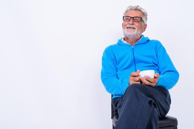 Homme barbu senior heureux réfléchi souriant tout en tenant une tasse de café et assis sur une chaise prête pour la salle de sport sur blanc