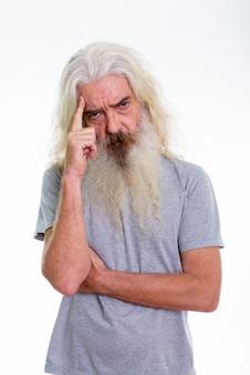 Homme barbu senior pensant avec le doigt sur la tête