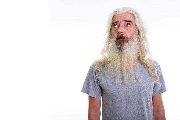 Homme barbu senior pensant en levant