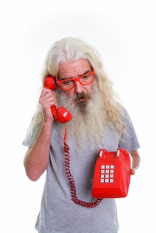 Homme barbu senior pensant et regardant vers le bas tout en parlant sur le vieux téléphone