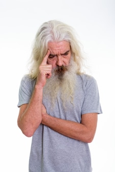 Homme barbu senior pensant en regardant vers le bas