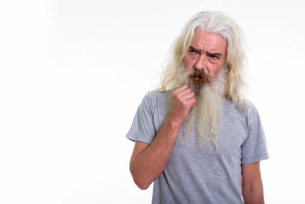 Homme barbu senior pensant tout en regardant triste