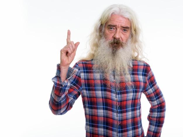 Homme barbu senior pointant le doigt vers le haut