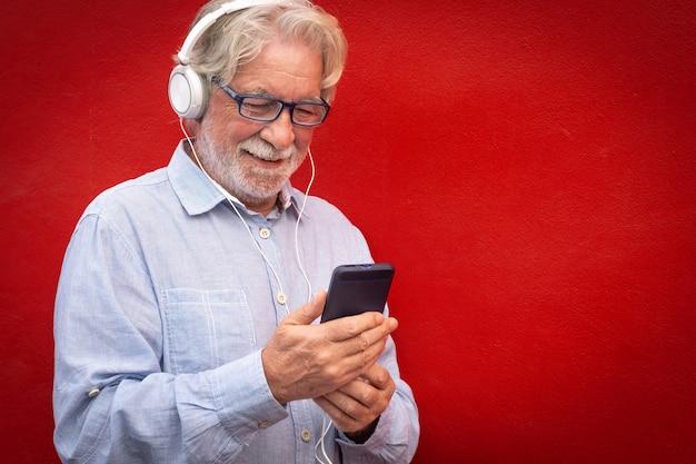 Homme barbu senior séduisant debout sur fond rouge portant des écouteurs écoutant de la musique à partir d'un téléphone intelligent. les gens de race blanche sourient sans soucis