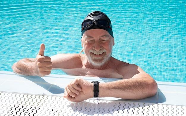 Homme barbu senior souriant gesticulant ok dans la piscine extérieure portant des lunettes et un bonnet de bain