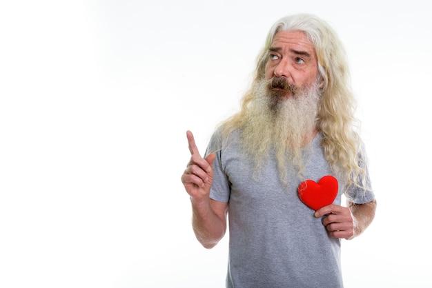 Homme barbu senior tenant un coeur rouge en pensant