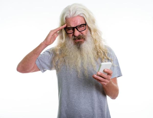 Homme barbu senior tenant un téléphone mobile